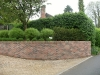 Border planted with rounded shaped shrubs to aestheically soften the wall lines