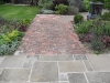 Reclaimed brick paving with Alchemilla mollis, Bergenias, Irises, Penstemons, Salvias and Lavender.