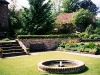 Georgian style sunken terrace with cottage style planning and formal circular water fountain