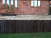 Reclaimed sleeper retaining wall for raised terrace