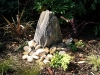 Monolith water feature in place, softened with rocks and cobbles and arhcitectural planting
