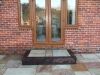 Single step built with reclaimed sleeper risers with stone paving tread