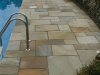 Pool side, natural stone paving cut on wall edge to meet desired curves