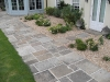 Reclaimed York stone path with traditional planting such as Santolina Edward Parker Bowles, Euphorbias, Irises, Verbascums, and Geraniums