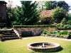 Georgian style sunken terrace with cottage style planting and formal circular water fountain